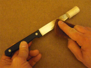 An old kitchen knife is prepared by covering the tip and cleaning the sides