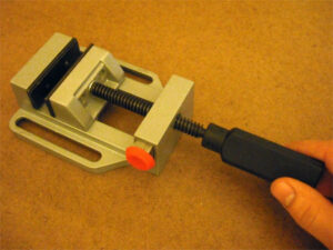A small vise is used to hold the knife during the fusing procedure