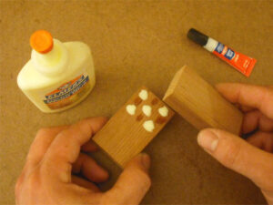 Super Glue is used to hold two pieces of wood together while the yellow wood glue cures