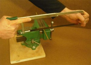 Using two hands to cut with a hacksaw. Extending the index finger of the hand that is on the handle seems to help.