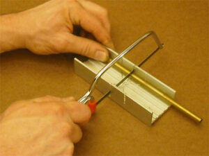 A miniature hacksaw and a small mitre box are used to cut brass tubing