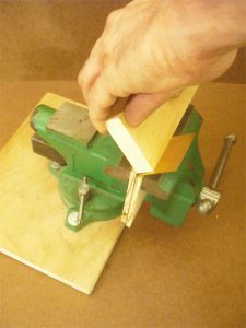 After clamping the sheet in a vise between two blocks of wood, a third block of wood is used to bend it