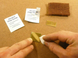 The brass parts are scoured with an abrasive pad, then cleaned with an alcohol swab
