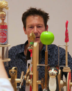 Stephen behind an automata kit made with an apple, cats, a barbie and a brasso can.