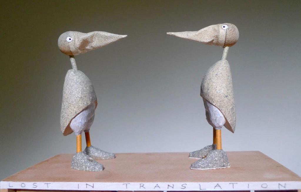 2 grey birds facing each other,.