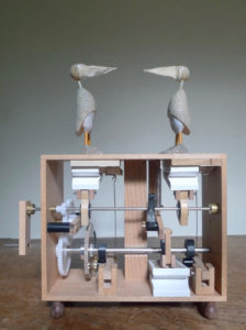 2 grey birds facing each other, on top of an open wooden box contains cogs & levers.
