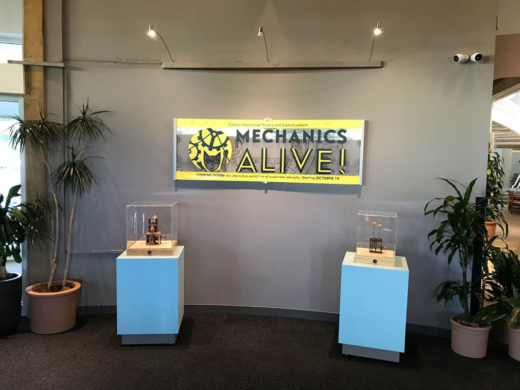 2 automata on plinths with mechanics alive sign on wall behind