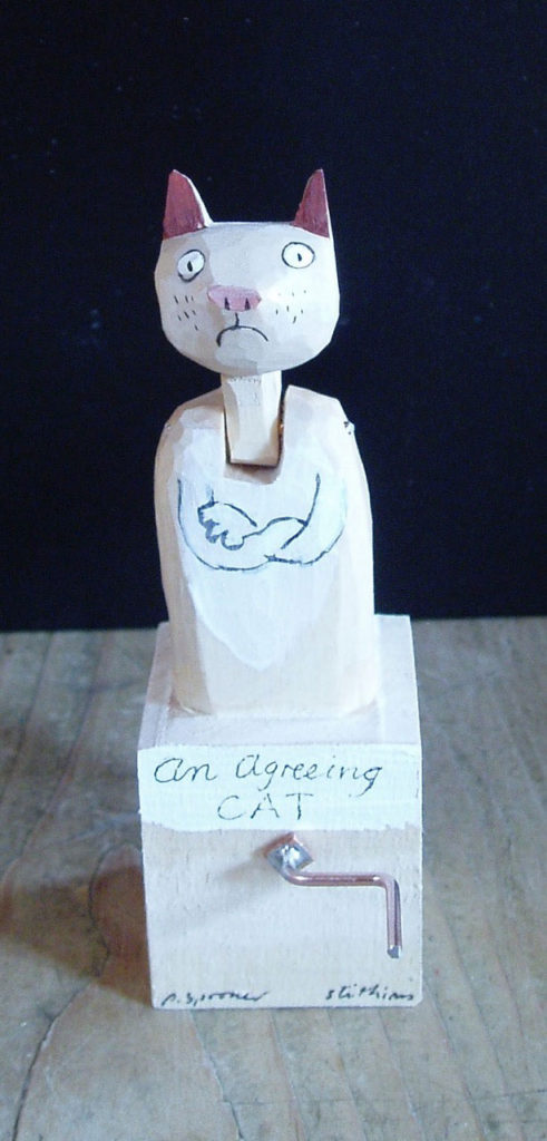 Painted wooden cat with arms crossed and head up
