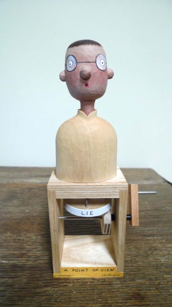 painted wooden figure on a box with the word lie beneath