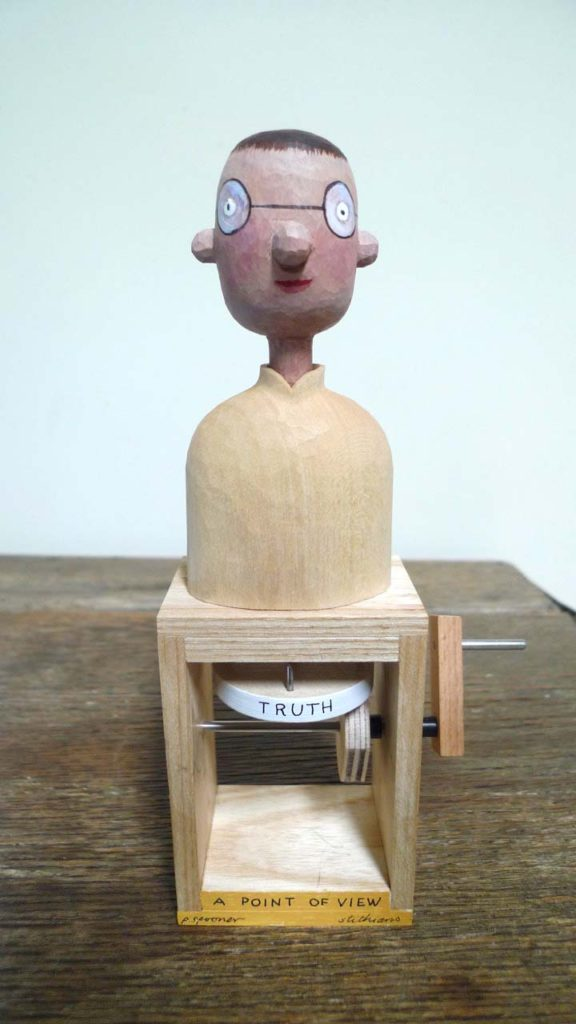 painted wooden figure on a box with the word truth beneath