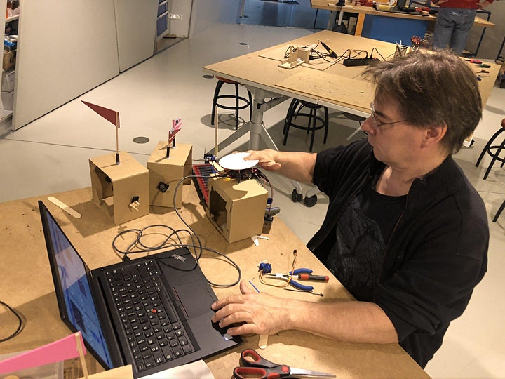 A man in a workshop at a computer with small automata and wires surrounding.