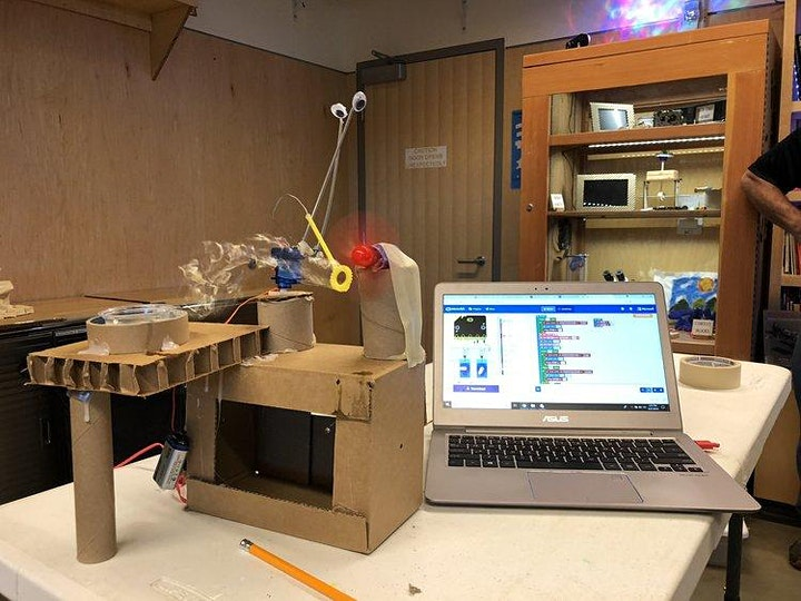 A laptop and automaton with google eyes.