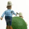 Carved wooden automata. 2 men in traditional cowboy outfits aim guns at each other either side of a grassy knoll. They alternate moving up and down.