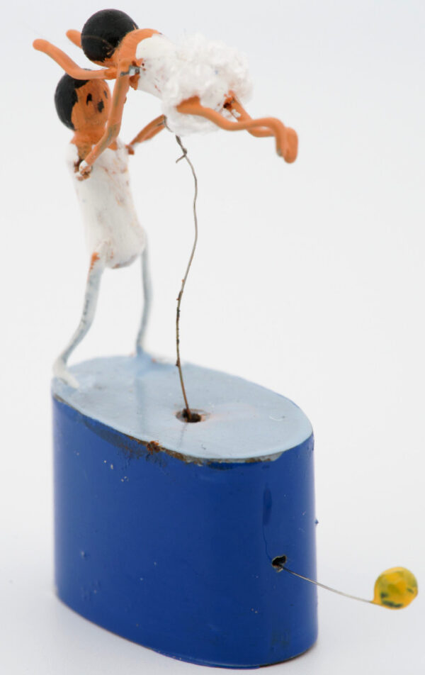 A miniature man in a white leotard lifts a woman in a ballet dress up in the air. They both have black hair and peach skin. They are mounted on a blue base with wire handle