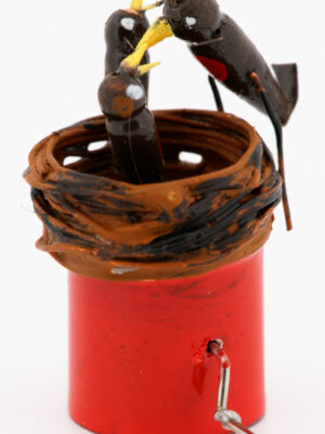 A miniature birds nest with 2 baby robins inside and an adult robin feeding them. Mounted on a red base with wire handle