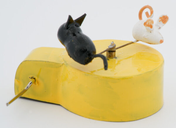 A miniature black cat chases a white mouse in a circle. Mounted on a yellow base with wire handle.