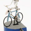A tiny skeleton rides a blue bicycle. The handlebars are made with a horned animal skull. It is mounted on a blue and grey base with metal handle.