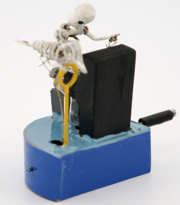 A white skeleton plays a black piano. There is a skeleton bird by his side. The characters are mounted on a blu base with a black handle.