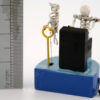 A ruler shows the height 30mm ne =xt to a miniature automata. A white skeleton plays a black piano. There is a skeleton bird by his side. The characters are mounted on a blu base with a black handle.